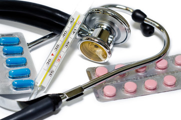 Medical stethoscope, thermometer and pills on white background.