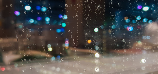 Drop  of water rain on window glasses surface with City light blur background.
