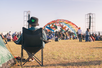 Back view of Man sitting chair on the grass, enjoying an outdoors music, culture, community event, festival,Funny group of young girls and boys at music festival, Happy teen at summer festival.