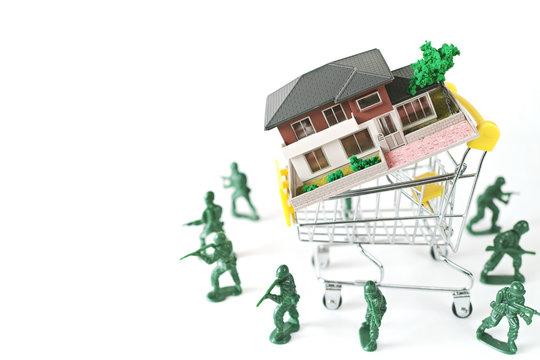 ミニチュアのショッピングカートに載せた家を守るミニチュア兵士