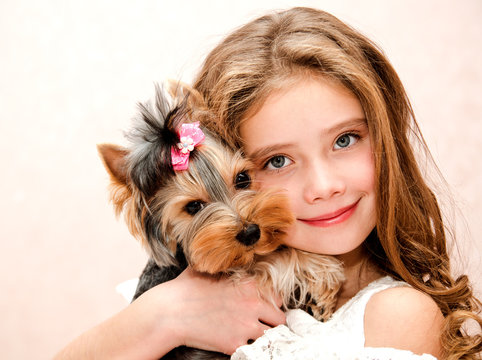 Adorable smiling little girl holding and playing with puppy yorkshire terrier