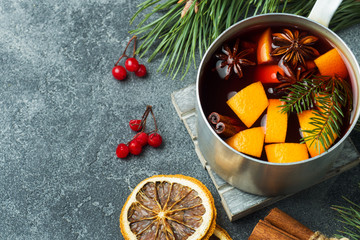 Christmas mulled wine with spices and fruit on the table. New year concept