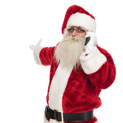 santa claus talking on the phone makes and inviting gesture