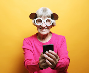 old grandmother is talking to her grandchildren by phone, smiling and greeting them.