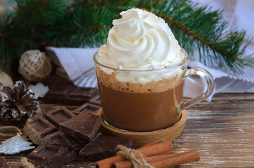 Delicious Cup of hot chocolate cocoa with whipped cream and chocolate crumbs on wooden table with  christmas decoration. Delicious winter beverage concept.