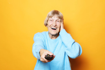 lifestyle and people concept: grandma is holding a TV remote over yellow background