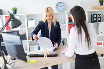 Two girls stand in the office bent over near the table and work with documents.