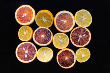 Bright slices of different citrus fruit on a black background