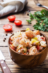 Stewed rice with chicken and vegetables in a wooden bowl.