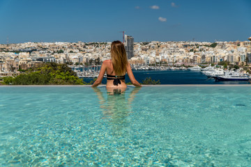 Blonde girl at the infinity pool in Malta