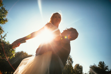 Dancing young bride and groom sunlight background