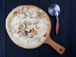Frozen pizza with porcini and truffle, on a wooden board, set on a dark blue background, flat lay