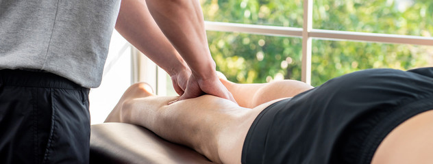 Male therapist giving leg massage to athlete patient in clinic