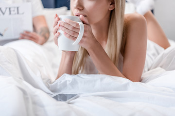 Young woman lying in bed and holding white coffee cup while man reading newspaper