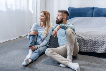 happy young couple sitting on floor and looking at window in blue bedroom