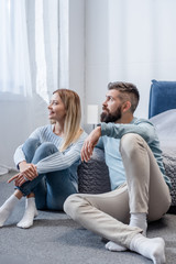 Young blonde girl and handsome bearded man smiling and sitting on floor in blue bedroom