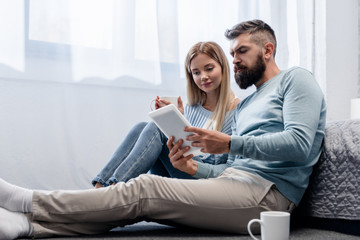 Couple sitting on floor with digital tablet and drinks