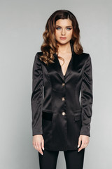 Portrait of stunning model with brunette wavy hair wearing classic black jacket with three buttons and looking at camera. Model has blue eyes. Isolate on grey.