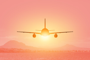 Poster Avion à Moteur Silhouette of airplane flying over the sea and beach at sunset. Travel concept.