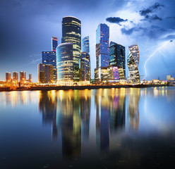Moscow Internation business centre at night with storm and lightning bolt, Russia