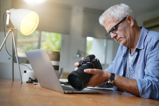 Mature photographer working in office