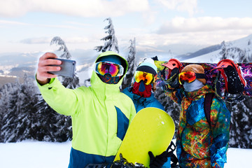 Three snowboarders taking selfie with smartphone camera at ski resort. Friends photographing for social network sharing with snowboards near forest wearing reflective goggles, colorful fashion clothes