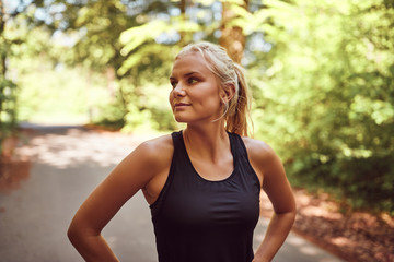Fit young woman standing on a forest path before jogging
