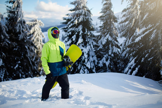 Snowboarder climbing to mountain top carrying his snowboard through forest for backcountry freeride and wearing reflective goggles, colorful fashion outfit and balaclava at ski resort. Winter sports.