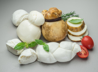 Mozzarella and Scamorza, traditional Italian cheeses with fresh herbs on gray background.