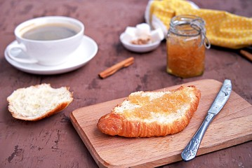 Breakfast: a cup of coffee, fresh croissant and orange jam