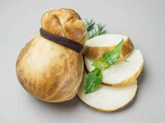 Traditional Italian smoked Scamorza cheese with herbs on gray background.