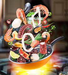 Flying seafood and spices falling into a frying pan. Flying motion effect of cooking process.
