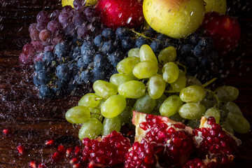 Grapes of several varieties, pomegranates, pomegranate seeds, apples on a wooden background with water splashes. Fresh fruit concept, new crop