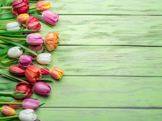 Colorful  bouquet of tulips on green wooden background.