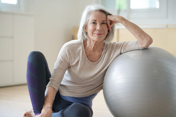 Smiling elderly woman resting on a swiss ball at home Fototapete