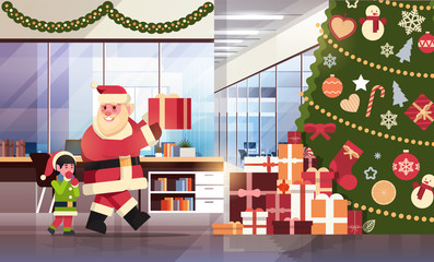 santa claus with elf helper put present under decorated fir tree in modern office merry christmas happy new year holidays concept flat horizontal