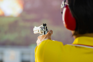 people hold a gun ready to shoot practicing shooting in the park (selective focus on the back part of gun)