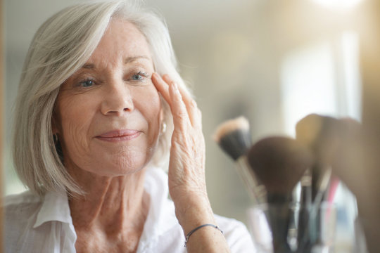 Attractive senior woman looking at herself in mirror