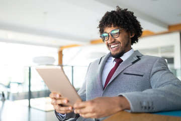 Smiling portrait of black businessman with touchscreen tablet device in office
