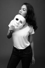 Portrait of young beautiful Asian woman holding mask
