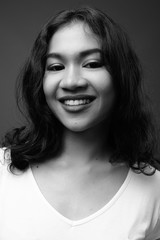 Face of young beautiful Asian woman smiling in black and white
