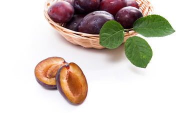 Yellow wooden basket with ripe plums, whole and half ripe plums isolated on a white background..