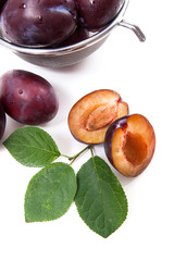 Steel colander with ripe plums, whole and half ripe plums with leaf isolated on a white background..