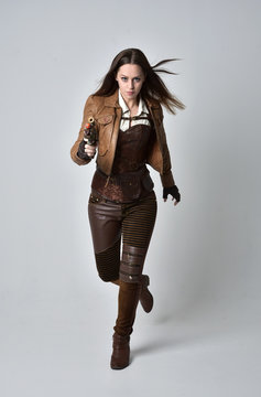 full length portrait of brunette  girl wearing brown leather steampunk outfit. standing pose, holding a gun. on grey studio background.
