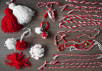 Martenitsa, white and red strains of yarn, Bulgarian folklore tradition, welcoming the spring in March, adornment symbol, wish for good health. Baba Marta Day. Pompons and bracelets.