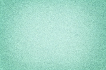 Texture of old light turquoise paper background, closeup. Structure of dense emerald cardboard.