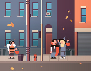 kids wearing monsters bee dracula wizard costumes walking town holiday concept tricks or treat happy halloween cartoon character full length horizontal flat