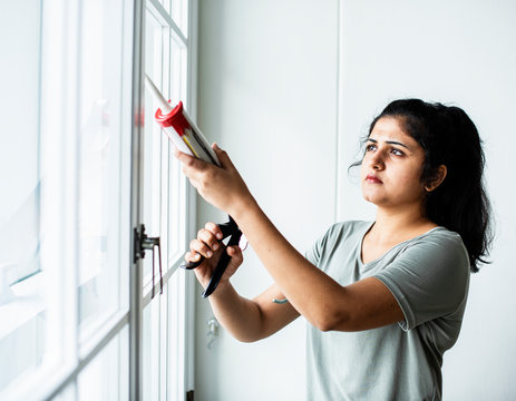 Woman using a silicone gun to repair a window
