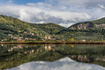 The characteristic village of Massaciuccoli is reflected in the waters of the homonymous lake, Lucca, Tuscany, Italy
