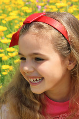 Happy girl smiling in a yellow flowers garden